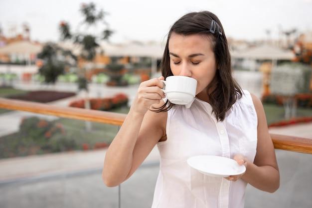 一杯のコーヒーと受け皿を手に屋外で朝を楽しんでいる魅力的な若い女性。休暇とレクリエーションの概念。