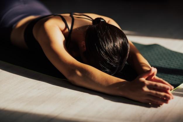 매력적인 젊은 여자가 집에서 운동하고, 바닥에 요가를하고, 거짓말을하고 훈련, 명상, 호흡 후 휴식