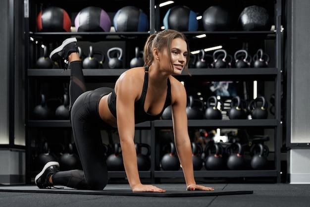 フィットネストレーニングを行使する魅力的な若い女性
