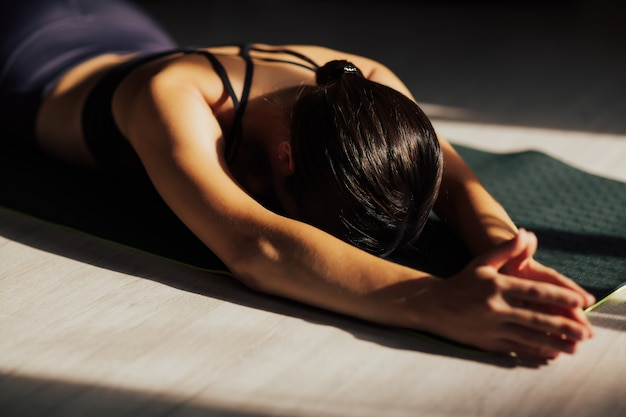 Attractive young woman exercising at home, doing yoga on the floor, lying and resting after training, meditation, breathing