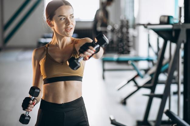 체육관에서 아령으로 운동 매력적인 젊은 여자