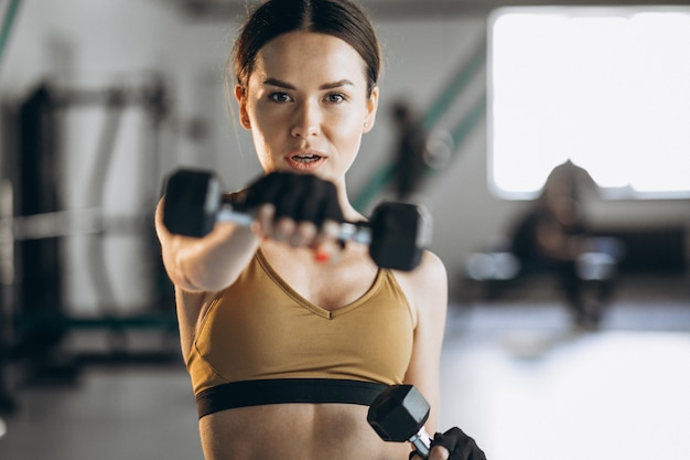 Attractive young woman exercising with dumbbells at the gym