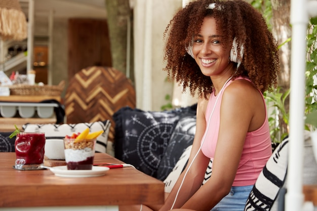 Attractive young woman feels excited as listens favourite song through white modern headphones accessory and smart phone, sits at cafe interior, surrounded with delicious desserts. entertainment