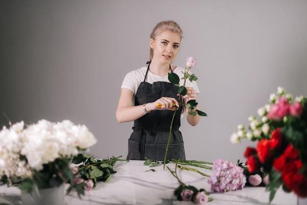 흰색 바탕에 신선한 장미를 가지고 작업하는 앞치마를 입은 매력적인 젊은 여성 꽃집