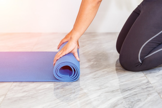 Attractive young woman folding blue yoga or fitness mat after working out at home in living room