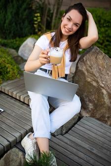 정원에서 노트북과 함께 앉아 점심 시간에 매력적인 젊은 여자 프리랜서.
