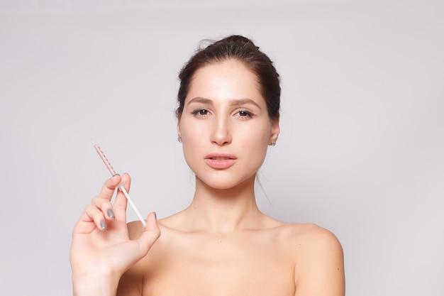 매력적인 젊은 여 자가 흰색 배경 위에 절연 화장품 주입을 가져옵니다. 여성의 손은 얼굴 근처에 주사를 위한 주사기를 들고 있습니다. 뷰티 트리트먼트.