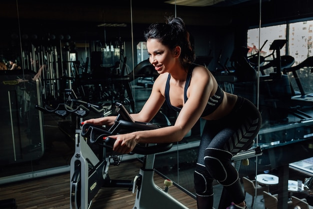 Attractive young woman at the gym riding on spinning bike.