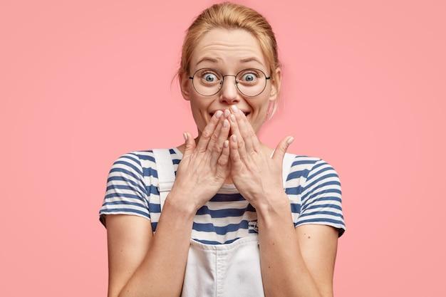 魅力的な若い女性は表情を大喜びし、両手のひらで口を覆い、目を飛び出し、カジュアルなtシャツとオーバーオールを着ています