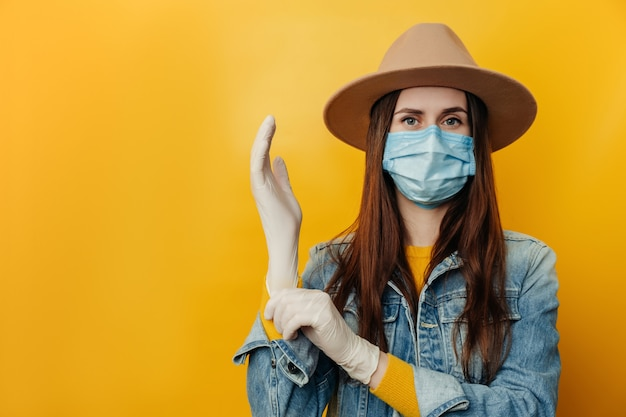 Attractive young woman in hat wears protective face mask, puts on medical gloves, preparing for a dangerous trip during the outbreak of a coronavirus epidemic, poses indoor against yellow background.