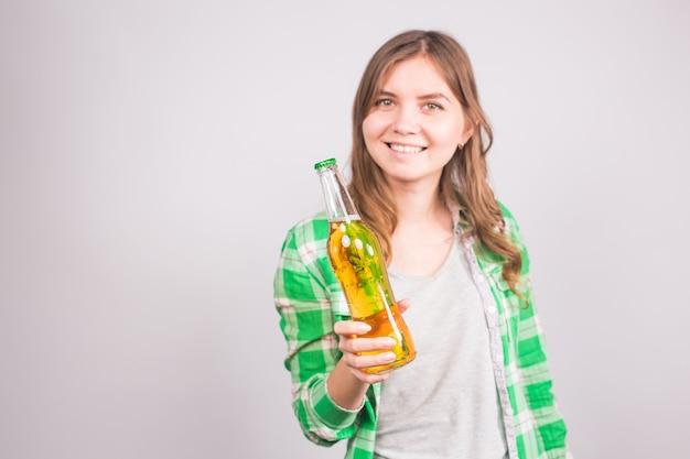 맥주 한 병을 들고 매력적인 젊은 여자.