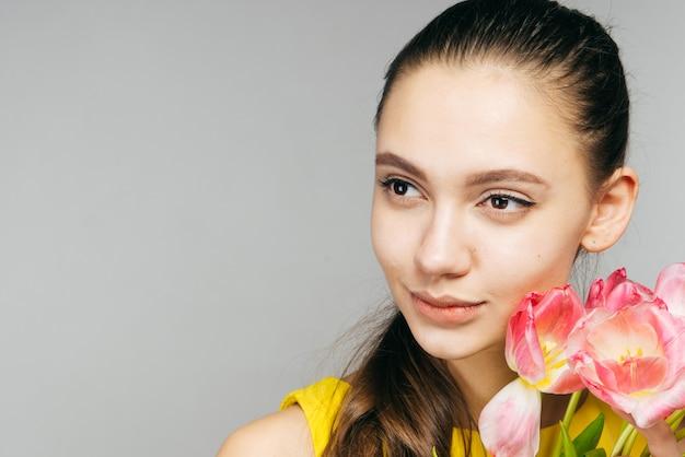 봄날 큰 꽃다발을 들고 있는 매력적인 젊은 여성