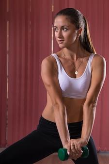 しゃがむ運動をしながら、フレームの左側を見ながらバーベルを保持している魅力的な若い女性。