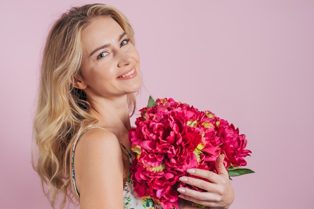 An attractive young woman holding beautiful red flowers against pink backdrop