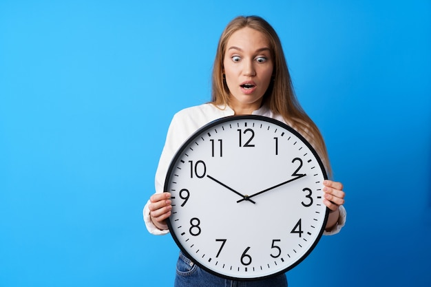 Привлекательная молодая женщина, держащая большие настенные часы на синем фоне
