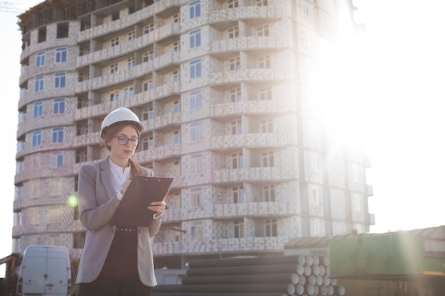 Attractive young woman holding clipboard during working at construction site