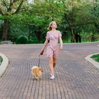 外で犬のスピッツを持ち、カメラに微笑み、公園を歩いている魅力的な若い女性。人と動物の友情のコンセプト。