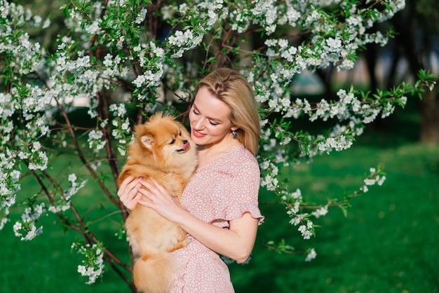 Привлекательная молодая женщина, держащая собачий шпиц на улице и улыбаясь в камеру, гуляет в парке