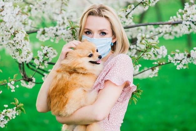 Привлекательная молодая женщина, держа собаку шпиц снаружи и улыбка на камеру, прогулки в парке.