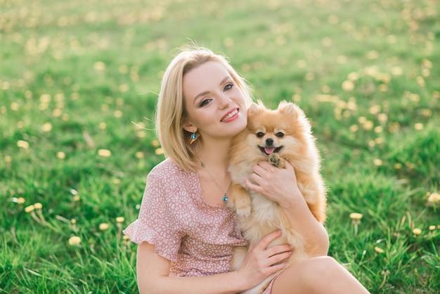 外で犬のスピッツを持って笑顔で公園を歩いている魅力的な若い女性。人と動物の友情についての概念。