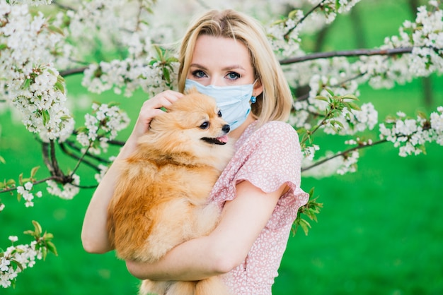 Attractive young woman holding dog spitz outside and smiling at camera, walking in the park.
