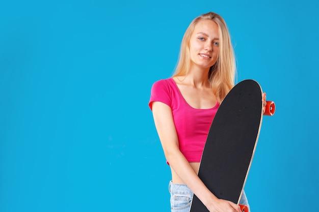 Привлекательная молодая женщина, держащая ее скейтборд на синем фоне