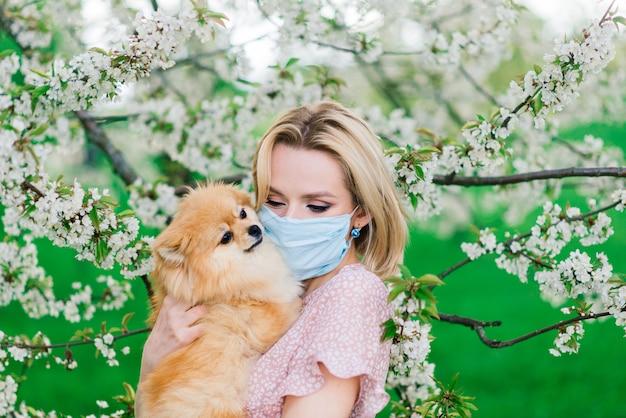 外スピッツ犬を保持している魅力的な若い女性