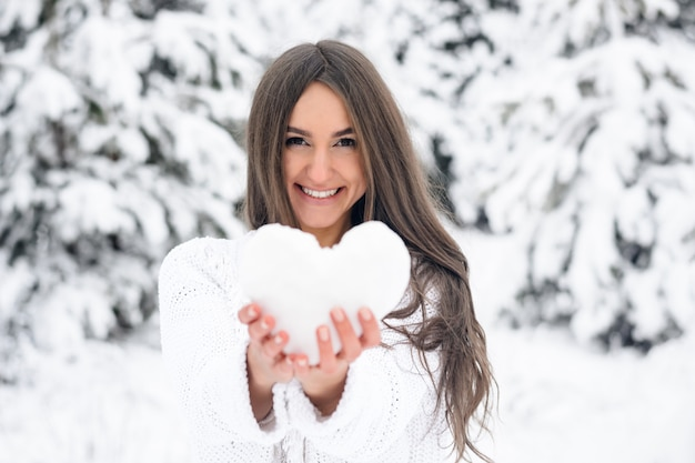 Attractive young woman holds a heart from the snow in the winter forest in the winter forest