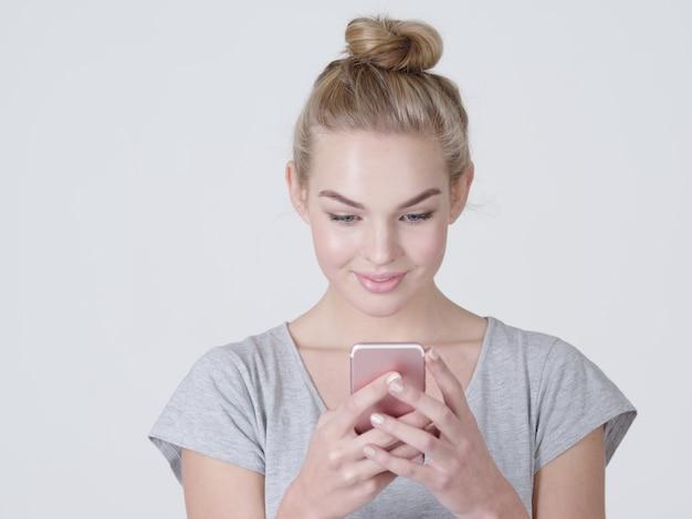 매력적인 젊은 여자 보유 휴대 전화-스튜디오