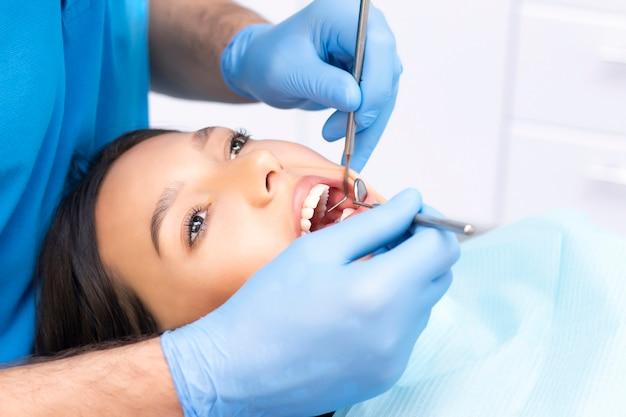 男性歯科医と歯科医院で魅力的な若い女性。健康な歯の概念。