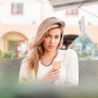 달콤한 아이스크림에 유행 흰색 니트 스웨터에 매력적인 젊은 여자는 야외 카페에 앉아있다. 아름다운 소녀는 꿈을 꾸고 주말을 즐깁니다.