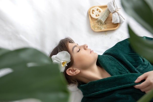 Привлекательная молодая женщина в зеленом халате лежит в спа-салоне, вид сверху.