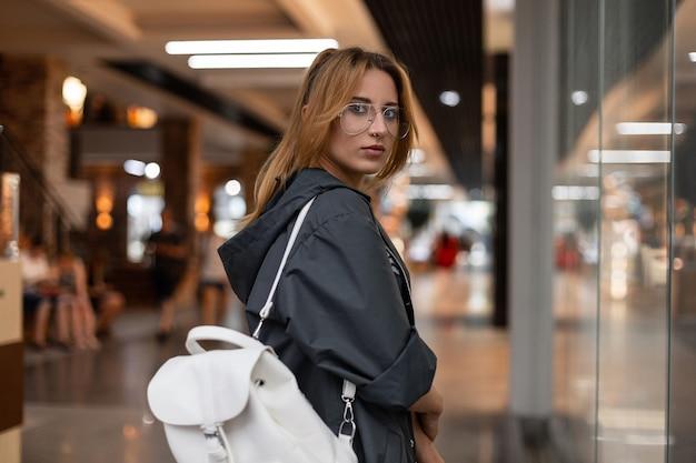 세련 된 흰색 가죽 배낭 유행 안경에 빈티지 비옷에 매력적인 젊은 여자는 쇼핑 센터에서 현대 유리 벽 근처 산책입니다. 아름다운 소녀. 청소년 스타일.