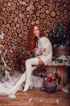 白いウールのセーターとニットの靴下を身に着けている冬のファッションショットで魅力的な若い女性