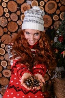 Привлекательная молодая женщина в зимней моде застрелила шерстяную белую кепку и красный шерстяной свитер