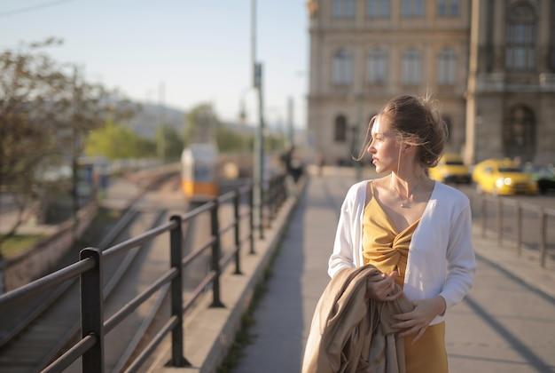 헝가리의 햇빛 아래 거리를 걷는 노란 드레스에 매력적인 젊은 여자