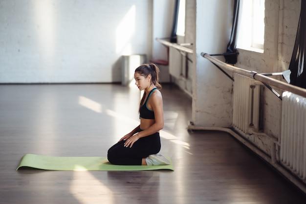 매트에 앉아 건강 한 라이프 스타일을 선택하는 activewear에 매력적인 젊은 여자. 체형 및 활동