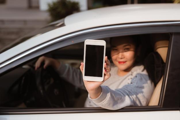 자동차에 있는 매력적인 젊은 여성은 빈 화면이 있는 스마트폰을 보여줍니다.