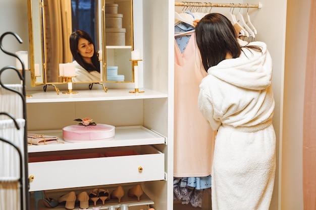 自宅の楽屋でドレスを選ぶバスローブの魅力的な若い女性