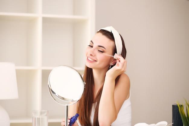 シャワーの後の浴室の魅力的な若い女性は、フェイスクリームで鏡の前に立っています。
