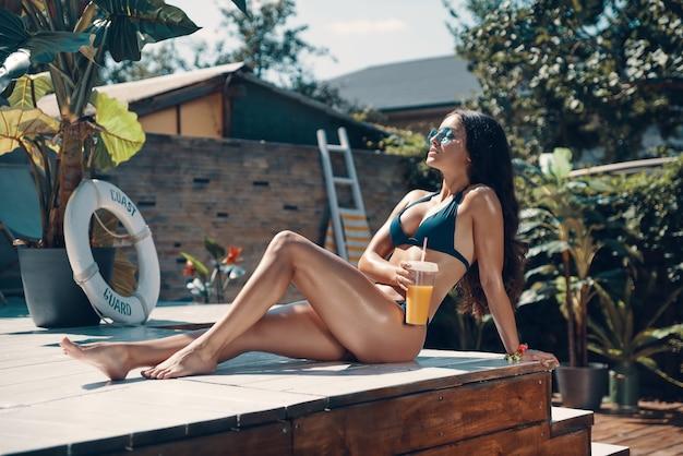 Привлекательная молодая женщина в бикини, пьющая коктейль и расслабляющаяся, сидя у бассейна на открытом воздухе