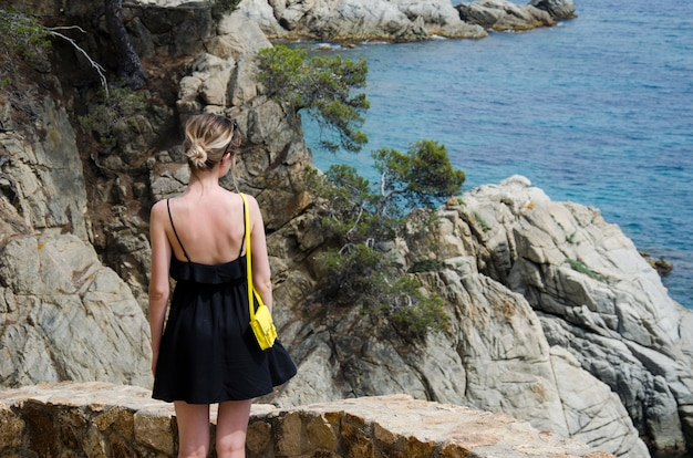 검은 드레스와 맑은 날에는 바다를 찾고 노란색 작은 가방으로 매력적인 젊은 여자. 검은 드레스 슬림 소녀 롤링 바다와 스페인, 로렛 드 마르의 아름다운 바위에 대 한 의미합니다.