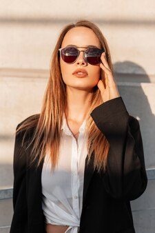 黒のスタイリッシュなブレザーを着た魅力的な若い女性は、サングラスをまっすぐにし、明るい日差しを楽しんでいます。夕暮れ時の街の建物の近くでポーズをとるカジュアルな古着の美しいかわいい都会の女の子。