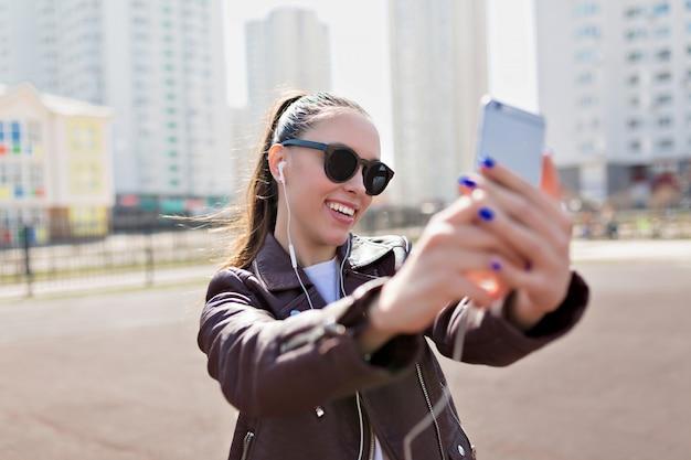 Привлекательная молодая женщина в черных очках и кожаной куртке делает селфи