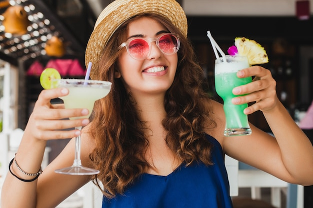 Привлекательная молодая женщина в голубом платье и соломенной шляпе в розовых солнцезащитных очках пьет алкогольные коктейли на тропических каникулах, сидя за столом в баре в летнем стиле, улыбаясь счастливой в партийном настроении