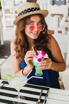 青いドレスとピンクのサングラスを着て麦わら帽子の魅力的な若い女性夏の衣装でバーのテーブルに座って、熱帯の休暇でアルコールカクテルを飲んでパーティー気分で幸せな笑顔