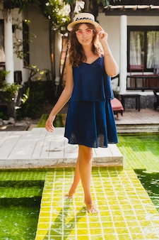 Привлекательная молодая женщина в синем платье и соломенной шляпе в розовых солнцезащитных очках гуляет у бассейна