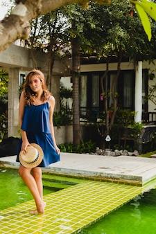 セクシーな夏のスタイルの衣装で休暇中に熱帯スパヴィラのプールで歩いているピンクのサングラスを身に着けている青いドレスと麦わら帽子の魅力的な若い女性