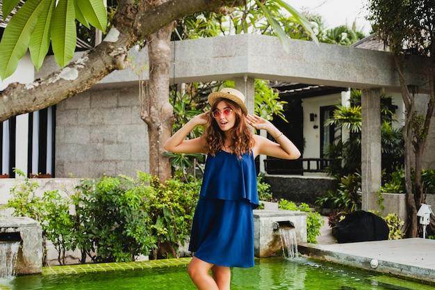 파란 드레스와 밀짚 모자에 매력적인 젊은 여자가 여름 스타일의 옷을 입고 휴가에 열대 스파 빌라의 수영장에서 산책하는 분홍색 sunglassses를 입고, 행복한 재미 미소