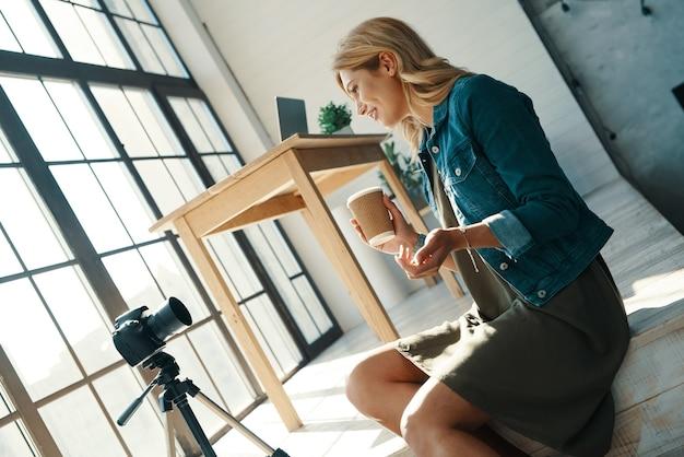 ビデオカメラの前で作業しながら笑顔のカジュアルな服を着た魅力的な若い女性